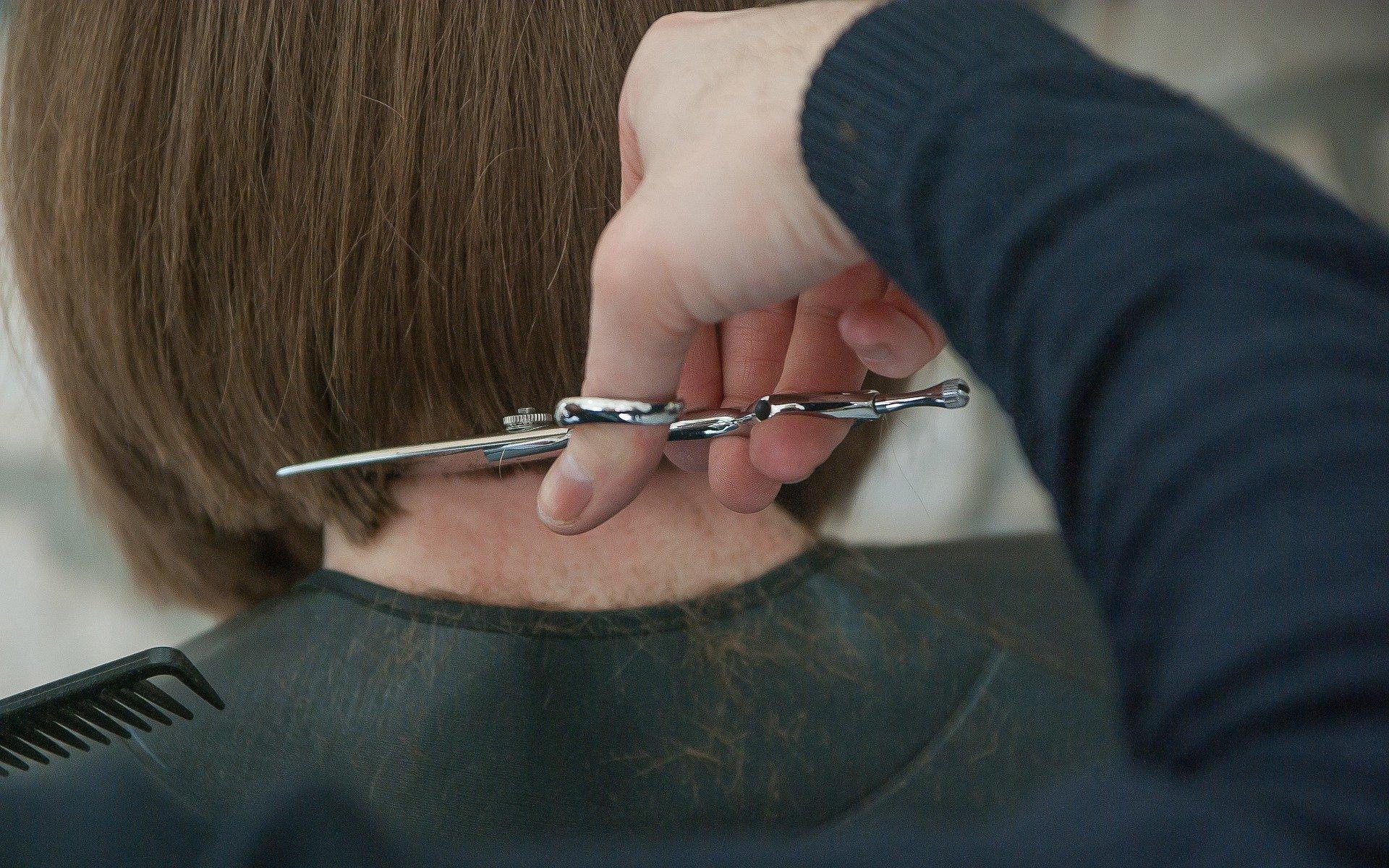 Eine Hand, die einer Frau die Haare schneidet