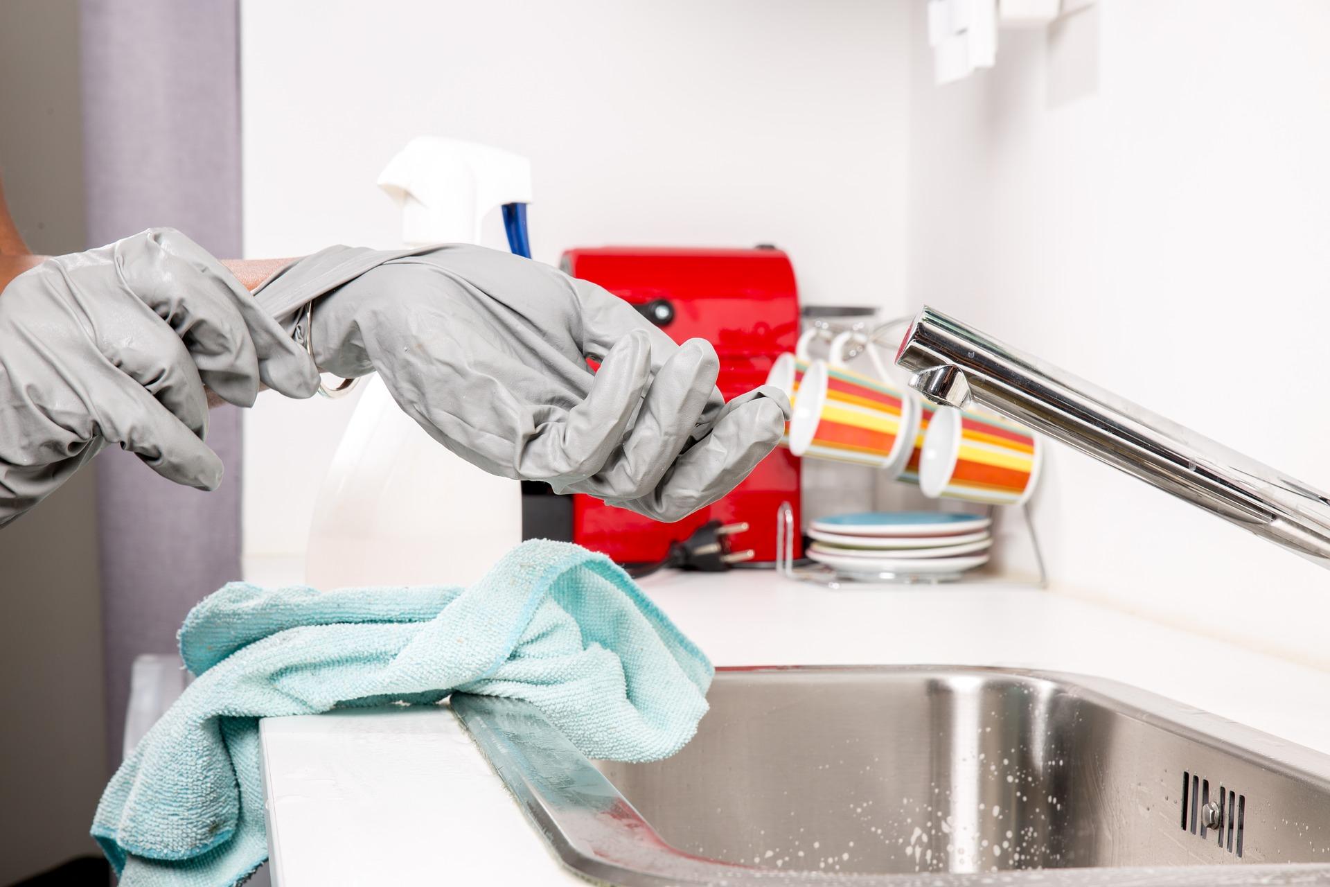 Hände mit Handschuhen bei einem Wasserhahn