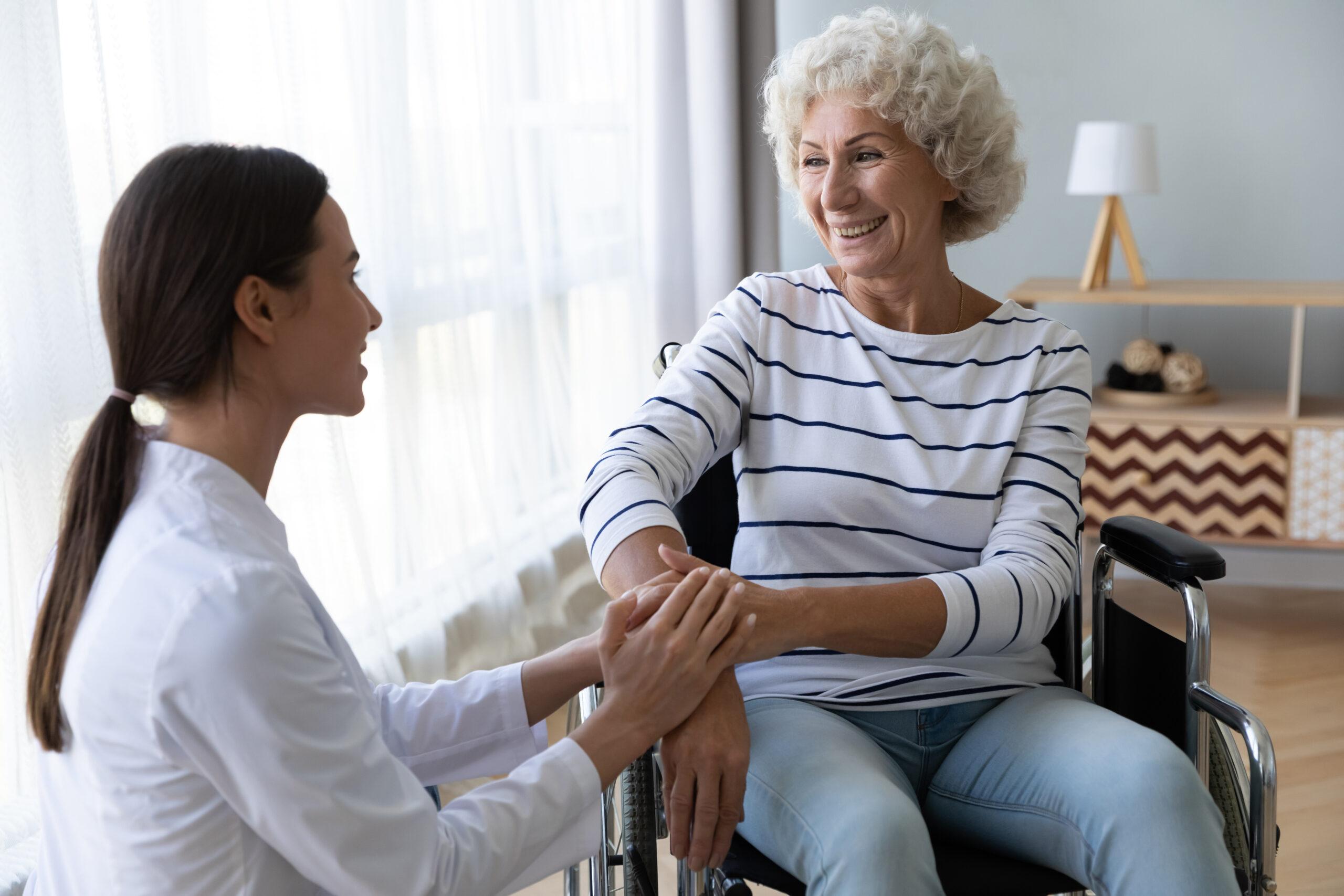 Eine Frau, die mit einer älteren Frau im Rollstuhl spricht