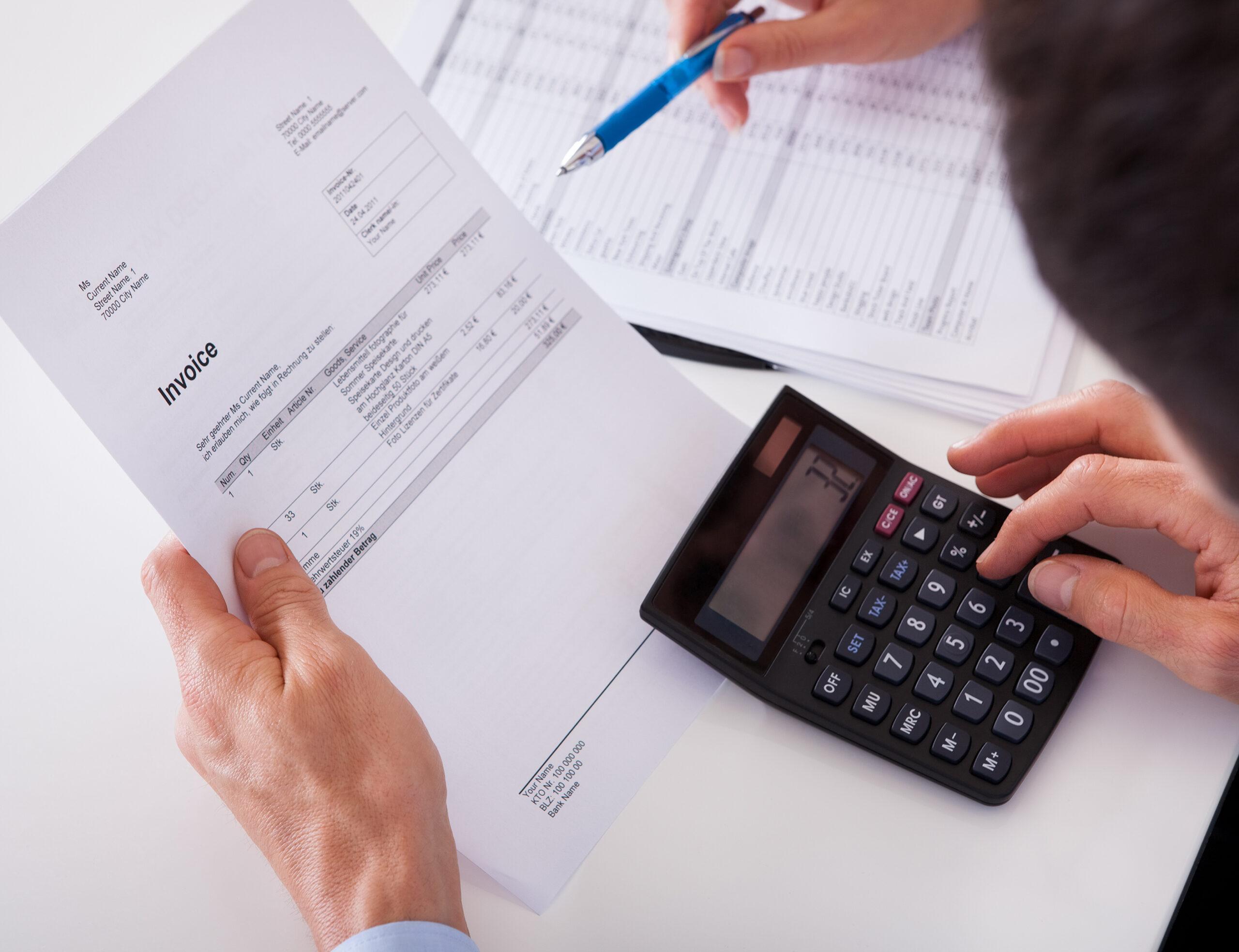 Ein Mann, der am Taschenrechner sitzt mit einer Rechnung in der anderen Hand