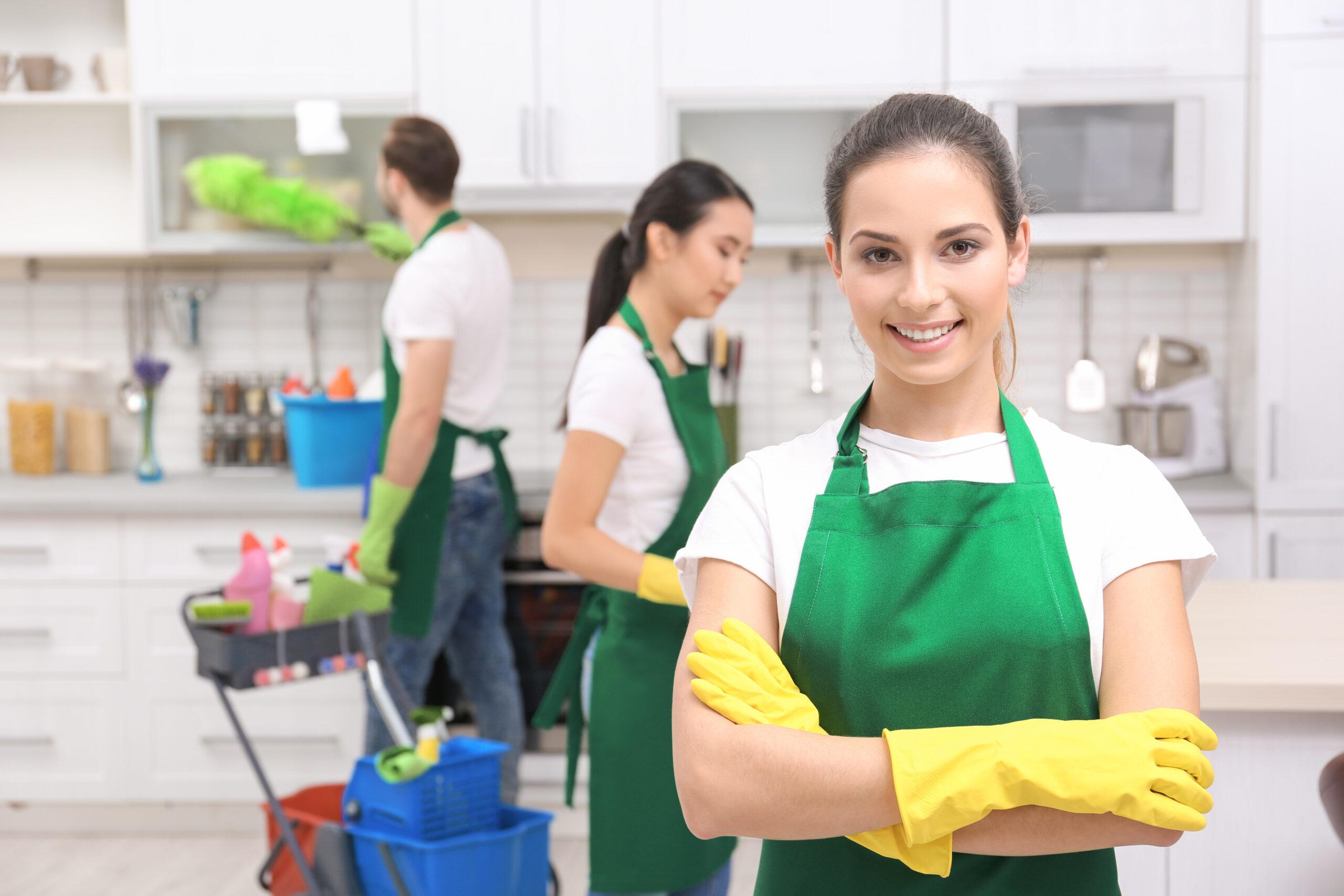Eine Frau mit grüner Schürze und gelben Handschuhen und im Hintergrund zwei Personen mit der selben Kleidung, die putzen