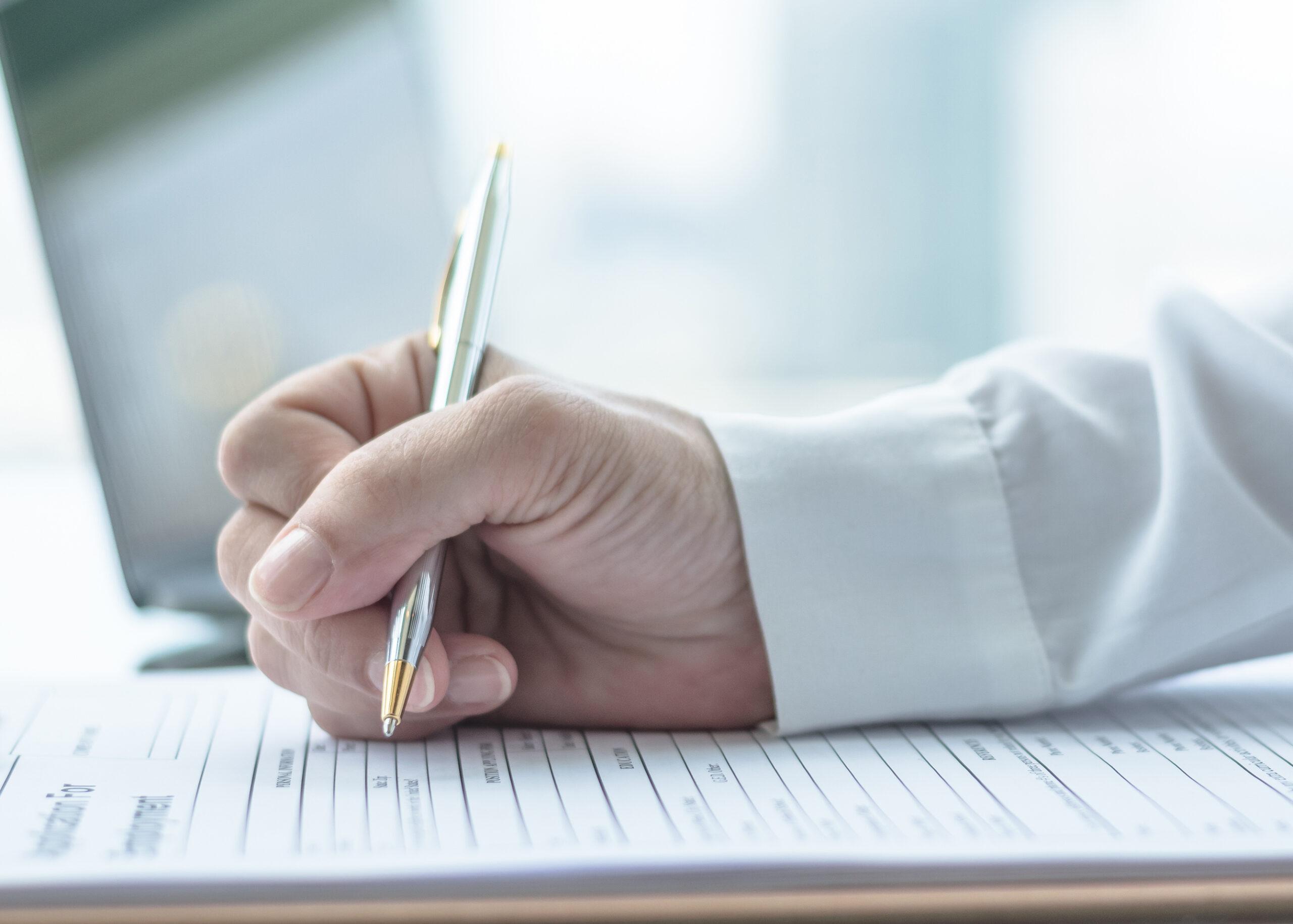 Eine Hand mit einem Stift, die ein Formular ausfüllt